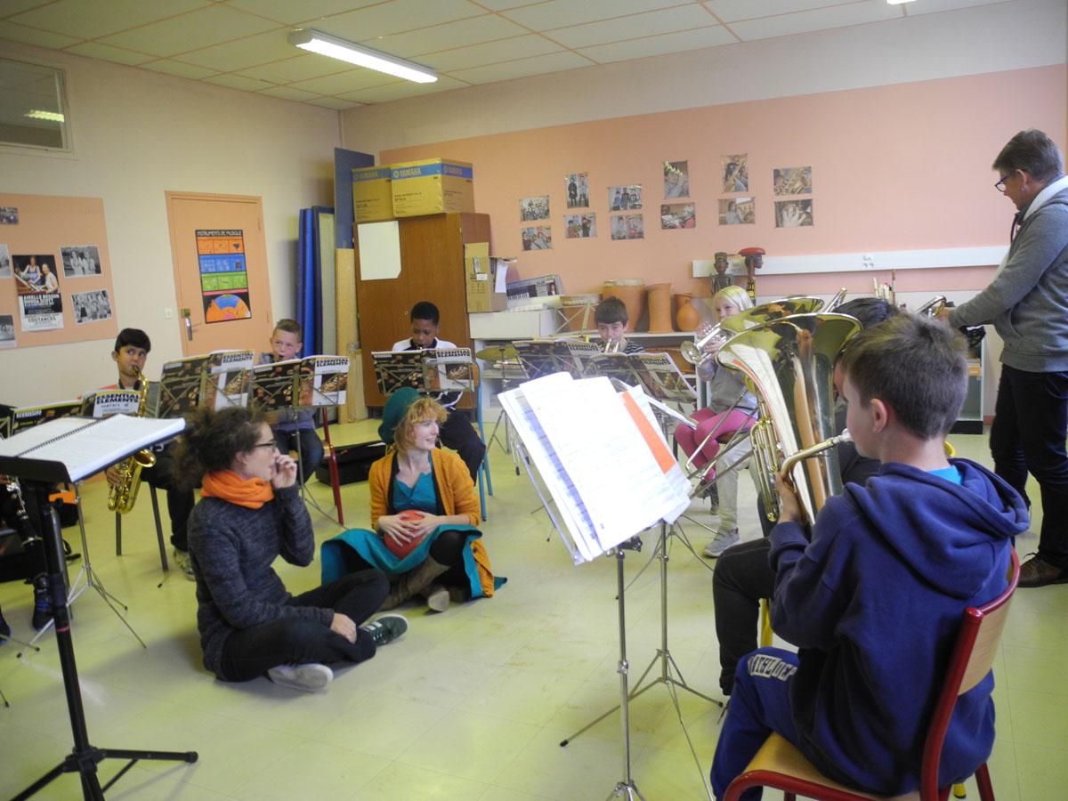 Les enfants de Claires Fontaines font de la musique avec Clémence qui tient le ballon.