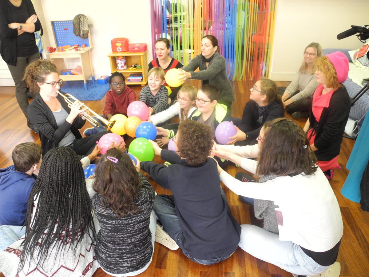 Airelle Besson joue un morceau devant les enfants qui tiennent les ballons pour sentir les vibrations.